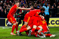 Joe Allen and Joe Morrell pile on as Aaron Ramsey of Wales celebrates scoring a goal to make it 2-0 - Rogan/JMP - 19/11/2019 - FOOTBALL - Cardiff City Stadium - Cardiff, Wales - Wales v Hungary - UEFA Euro 2020 Qualifiers.