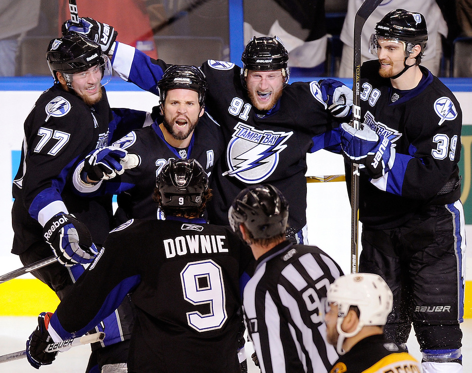 Tampa Bay Lightning's Martin St. Louis, second from left, along with teammates Victor Hedman, left, Steve Stamkos, Mike Lundin, far right, and Steve Downie, bottom celebrate St. Louis' third period goal as Boston's Mark Recchi skates towards the bench Wednesday, May 25, 2011 in Tampa.