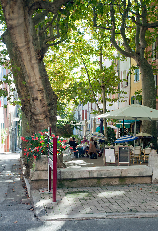 Outdoor cafe in Place Capitaine Vincens in Barjols with Fontaine du Champignon (mushroom fountain) in background.  This Provencal Verte town in the Var region of southern France is noted for its numerous fountains, wash houses, and old tanneries, a town shaped by water since Roman times.