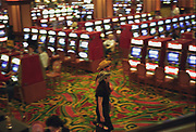 Stetson wearing couple walking through a mass of slot machines in a casino, Las Vegas, USA, 2000's