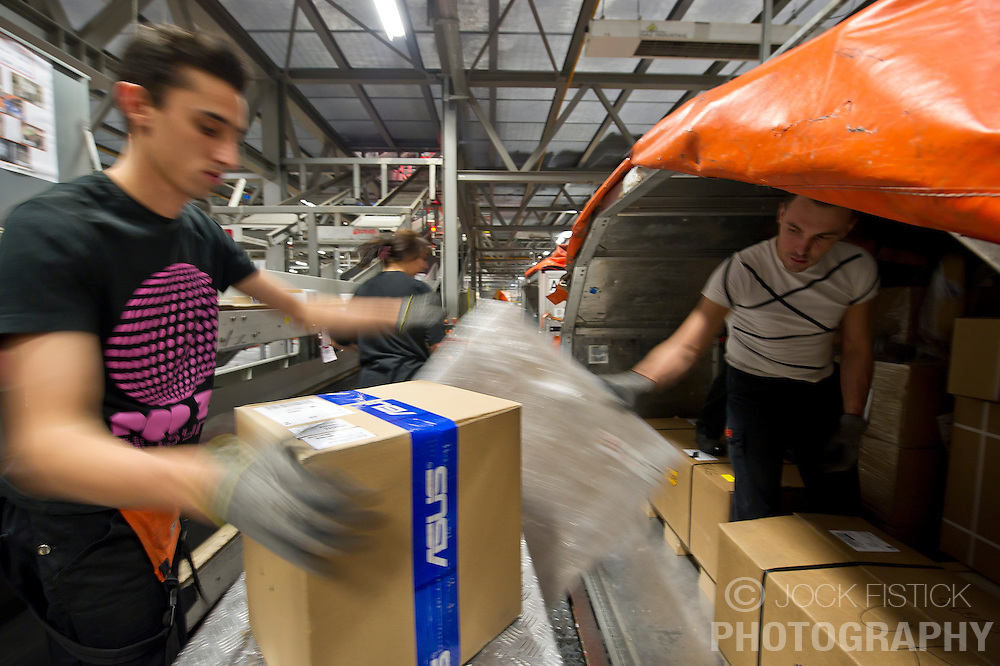 Employees from TNT Express Worldwide S.A. process incoming and outgoing freight on Friday July 23, 2010, at the Liège Airport in Grâce-Hollogne, Belgium. Approximately  90,000 packages move through TNT's main European hub every night. (Photo © Jock Fistick)