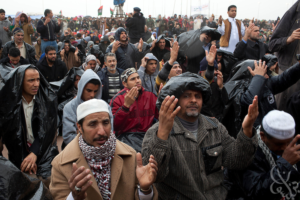 Libyan opposition supporters gather for a rainy Friday prayer in the central square March 04, 2011 in Benghazi, Libya.  Opposition protests took place in both eastern Libya and Tripoli on Friday, and late in the day an explosion rocked a base near Benghazi killing at least 30 and wounding more than 60. .Slug: Libya.Credit: Scott Nelson for the New York Times