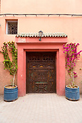 MARRAKESH, MOROCCO - 19TH APRIL 2016 - Old wooden doorway with colourful greenery planted either side in the Marrakesh old medina, Morocco.