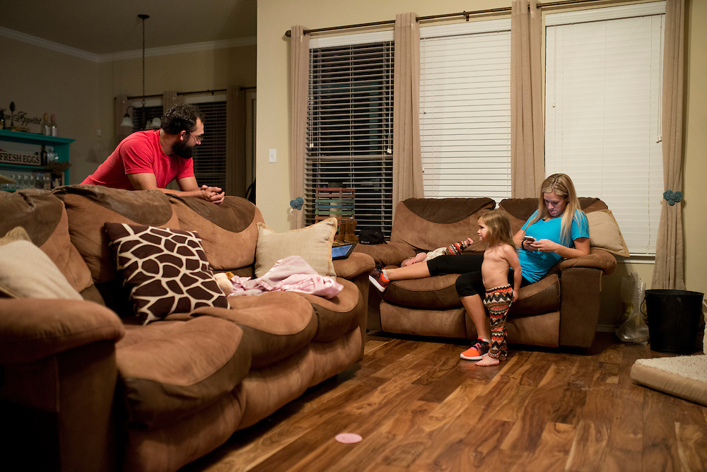 Johny Hendricks and his wife Christina talk with their daughter Adli, 2, while their eight-month-old daughter, Avin, lays on the couch at their home in Midlothian, Texas on February 27, 2014.