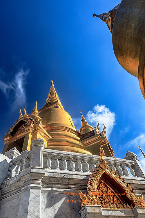 Surrealistic Stupas: An unusual, low wide angle view looking up at Tritotsathep Temple with two golden Stupas, one rising vertically, the second appearing to enter the scene horizontally, , Bangkok Thailand.