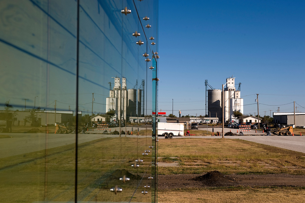 """Greensburg, Kansas, USA..Reflexion of the grain silo in the glass panels of 5.4.7 Art Center..The 5.4.7 Arts Center takes their name from the date of the tornado that devastated Greensburg on May 4, 2007. It is the first LEED Platinum building designed and constructed by students, and is the first LEED Platinum certified structure in the state of Kansas. The building earned the LEED Platinum certification through its use of wind turbines, photovoltaic panels, geothermal climate control, recycled building materials and a host of other ecologically minded features. The 5.4.7 Art Center is a community arts center to raise awareness of fine arts, both visual and performing, making arts accessible to everyone and provide an environment to create and gather knowledge through classes, exhibits and performances. """"The arts are extremely important to our community in order to maintain and cultivate our identity, our heritage, and our culture.""""..""""Greensburg: Better, Stronger, Greener!"""".On May 4, 2007, an EF5 tornado cut a 1.7-mile path of destruction through Greensburg, Kansas. Winds reaching speeds of 205 miles per hour uprooted trees, demolished homes and leveled the town. Eleven people died and 95% of the buildings were destroyed beyond repair. Residents have since worked furiously to rebuild it in a way that is both economically and environmentally sustainable and to meet the highest environmental standards. Greensburg, whose population has dropped from about 1400 to 800 following the storm and is now growing again, is currently the greenest town in America and the first in the United States to pass a resolution to certify that all city-owned buildings earn LEED Platinum accreditation, the highest level of the LEED rating system...Foto © Stefan Falke"""