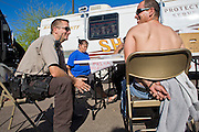 03 APRIL 2008 -- GUADALUPE, AZ:  Maricopa County deputies process people they apprehended during a zero tolerance crime sweep targeting primarily illegal immigrants in Guadalupe, AZ. The Maricopa County Sheriff's Department has started high profile zero tolerance crime sweeps targeting illegal immigrants but also arresting anyone they find breaking the law or with outstanding warrants. All of the previous sweeps have been in Phoenix city limits. This was the first one outside Phoenix, Guadalupe is a working class unincorporated town south of Phoenix. Most of the town's residents are Native Americans and Hispanics and hundreds of people lined the street to protest the sweep.  In 2011, the US Department of Justice issued a report highly critical of the Maricopa County Sheriff's Department and the jails. The DOJ said the Sheriff's Dept. engages in widespread discrimination against Latinos during traffic stops and immigration enforcement, violates the rights of Spanish speaking prisoners in the jails and retaliates against the Sheriff's political opponents.     PHOTO BY JACK KURTZ
