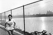 A jogger running wearing a 'Topless Disco' T-shirt, Jeggers Reservoir Circuit, Central Park, New York, USA, 1980's.