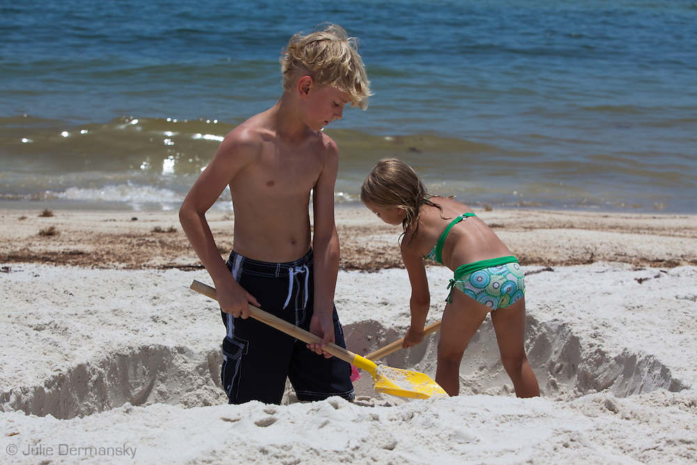 June 12, 2010,Orange Beach, Alabama, Braddon and Maci Thomas dig a big whole on the beach while BP oil washes on to the shore.