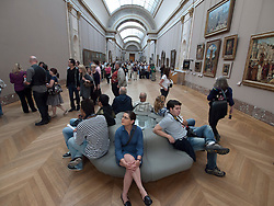 Interior of corridor full of tourists in The Louvre museum in Paris France