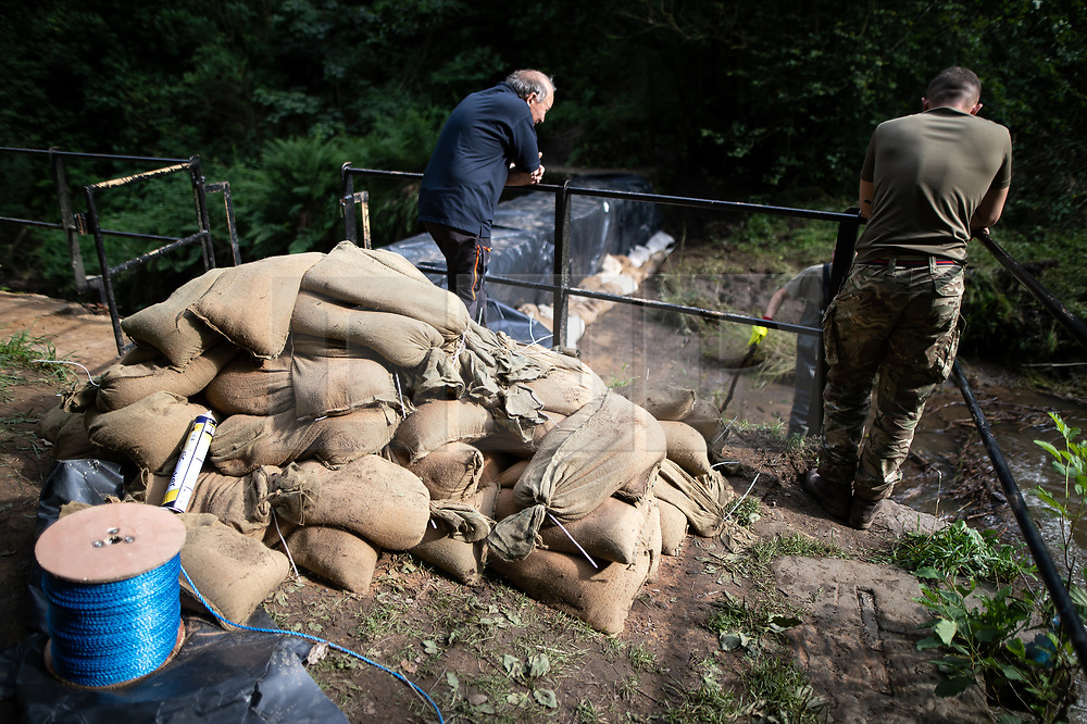 © Licensed to London News Pictures. 04/08/2019. Whaley Bridge, UK. Sandbags left at the side of the dam . The upstream river that feeds the Toddbrook Reservoir is diverted in to a bywater via a sluice and a dam is increased in height by 1 metre , leaving the riverbed that feeds the reservoir dry . More rain is forecast overnight (Sunday 4th/Monday 5th August) in the town of Whaley Bridge in Derbyshire after earlier heavy rain caused damage to the Toddbrook Reservoir , threatening homes and businesses with flooding. Photo credit: Joel Goodman/LNP