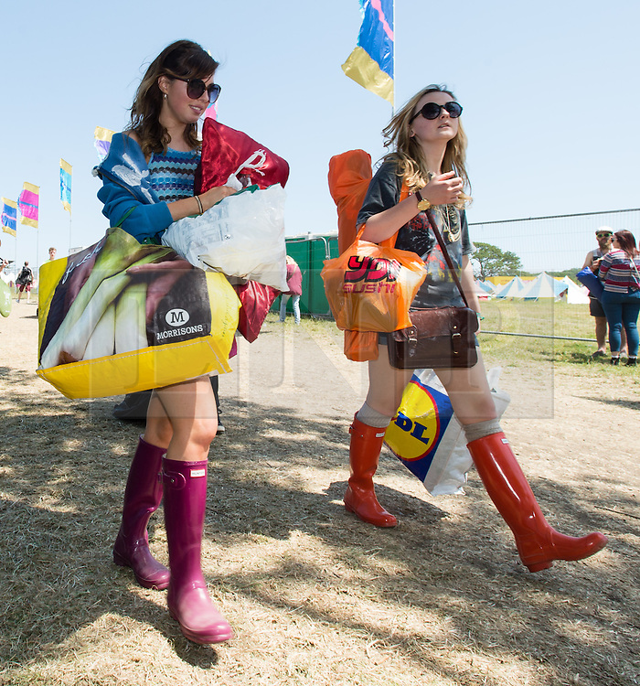 © Licensed to London News Pictures. 11/06/2015. Newport, UK.  Festival goers wearing brightly coloured wellies arrive at the Isle of Wight Festival 2015 carrying their tents and belongings just after being allowed onto the campsite at midday. This years festival include headline artists the Prodigy, Blur and Fleetwood Mac.  Photo credit : Richard Isaac/LNP