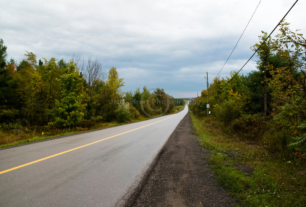 Moody skies over paved, wet rural road that leads towards city