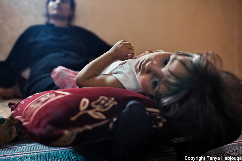 Aysha rocks her youngest daughter to sleep, while nervously waiting for news of her husband.