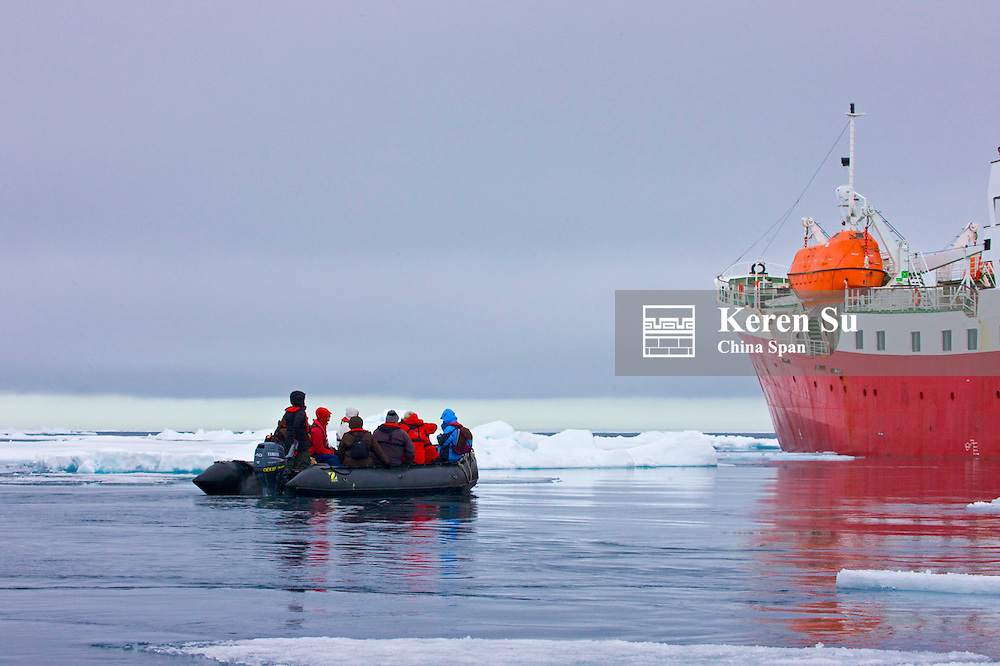Cruise ship and zodiac with floating ice in the Arctic Ocean, Sorgfjord, Spitsbergen, Norway