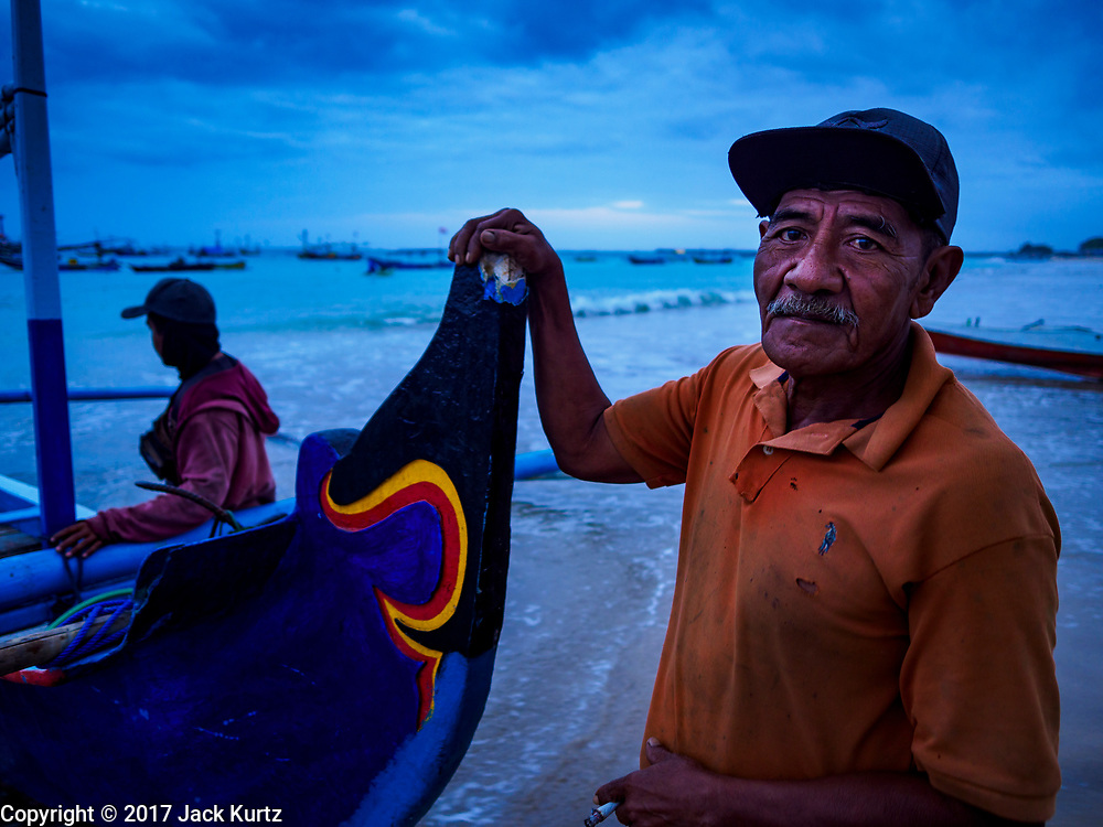 03 AUGUST 2017 - KUTA, BALI, INDONESIA: A fisherman with his outrigger canoe on Jimbrana Beach in Kuta. The beach is close to the airport and a short drive from other beaches in southeast Bali. Jimbrana was originally a fishing village with a busy local market. About 25 years ago, developers started building restaurants and hotels along the beach and land prices are rising. The new emphasis on tourism is changing the nature of the area but the fishermen are still busy very early in the morning.     PHOTO BY JACK KURTZ