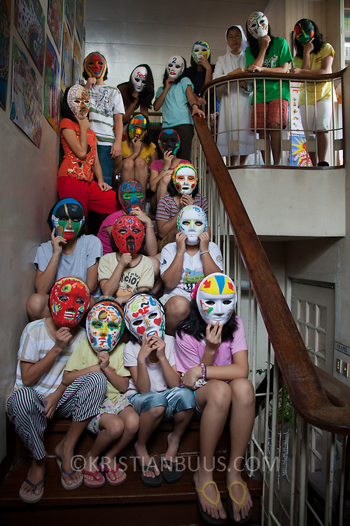 Residents of the Laura Vicuña Center in Manila. The Laura Vicuña Centre in Cubao houses 30 street girls, who may be orphaned, neglected, abandoned, battered, morally endangered and abused. The girls are aged between 6 and 16 and all of them go to school in the local school. To protect the girl's identity they have all been photographed partially covering themselves with masks they have made in art therapy. Laura Vicuña is a non-profit charity working in Manila and in Bacolod in the province of Negros Occidental in the Philippines.