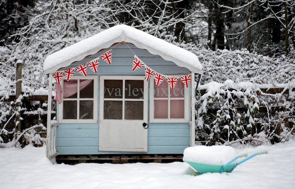 24 December 2009. Catterick, North Yorkshire, Great Britain. <br /> A child's Wendy house sits in a snowy garden replete with miniature Union Jack flags. <br /> Photo; Charlie Varley.