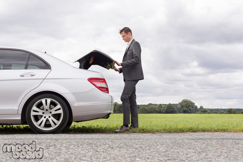 Full length side view of young businessman opening broken down car trunk at countryside