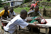 A Liberian man is rushed to hospital after being shot in the head in the Mamba point district, whilst mortar bombs exploded all around the area, Monrovia 27 July 2003. Fierce fighting continued today after government forces drove LURD(Lieberians United for Reconciliation and Democracy) rebels back over the 'Old Bridge' which leads into monrovia. This is the ninth day of continued fighting in Monrovia.<br /> EPA PHOTO/NIC BOTHMA