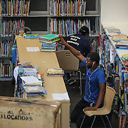 WASHINGTON, DC - SEP9: Darnell Matthews and Denise Barnes, library technicians, shelve books for the opening of the new Woodridge Public Library, the latest library to reopen in D.C. with an innovative design, September 9, 2016. (Photo by Evelyn Hockstein/For The Washington Post)