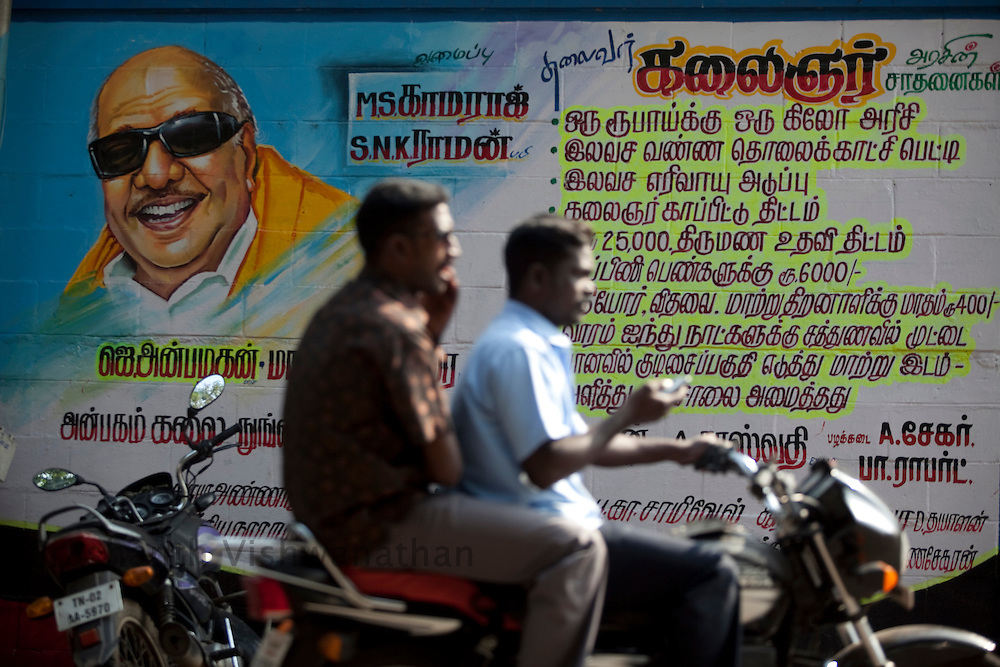 A motor cylce passes a election poster painted with Tamilnadu, Chief Minister, M. Karunanidhi on a road in Chennai, India, on Thursday, January 13, 2011. Karunanidhi began his career as a screenwriter in the Tamil film industry. Through his wit and oratorical skills he rapidly rose as a popular politician. He was famous for writing historical and social (reformist) stories which propagated the socialist and rationalist ideals of the Dravidian movement to which he belonged. Photographer: Prashanth Vishwanathan/HELSINGIN SANOMAT