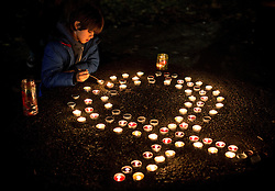 "© Licensed to London News Pictures . 01/12/2013 . Manchester , UK . A boy kneels beside candles arranged in the shape of a ribbon , in the park . World AIDS Day commemoration in Sackville Park , Manchester , this evening (Sunday 1st December 2013) including a candle-lit procession around the city's "" Gay Village "" . Photo credit : Joel Goodman/LNP"
