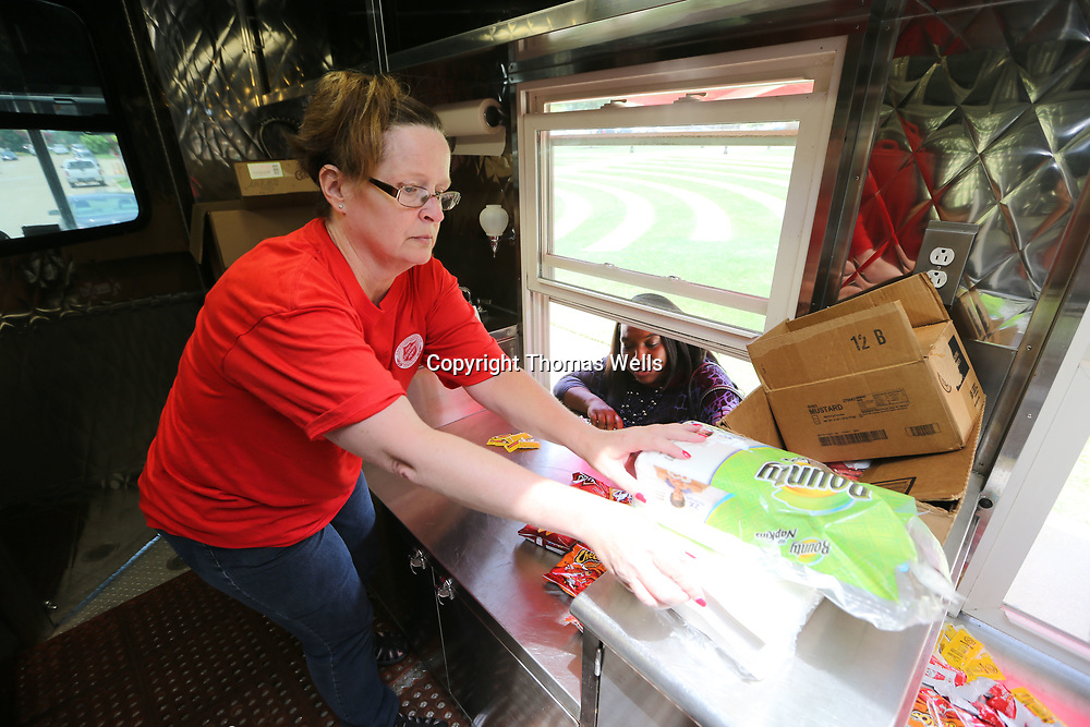 Salvation Army employee Susan Gilbert hands out free hot dogs at Fairpark on Wednesday in Tupelo.
