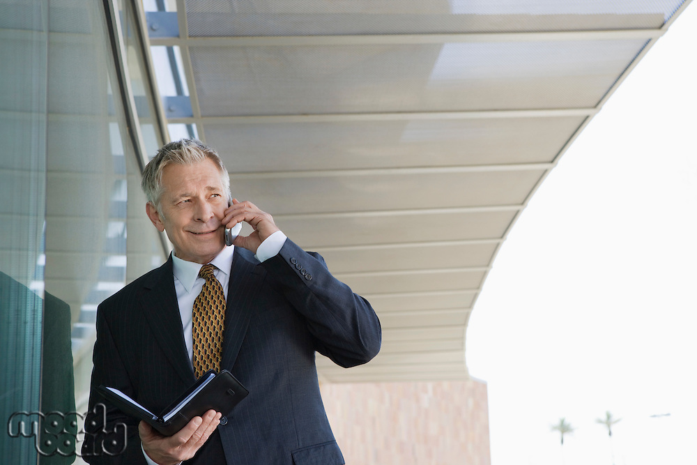 Businessman using cell phone holding day planner