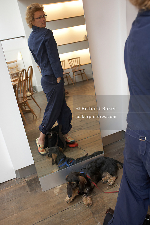 A customer tries on a jacket with pet dog at British couturier Margaret Howell's flagship Wigmore Street London shop