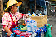 06 JUNE 2013 - BANGKOK, THAILAND:    A drink vendor waits for customers on Krung Kasem Road in Bobae Market. Bobae Market is a 30 year old famous for fashion wholesale and is now very popular with exporters from around the world. Bobae Tower is next to the market and  advertises itself as having 1,300 stalls under one roof and claims to be the largest garment wholesale center in Thailand.       PHOTO BY JACK KURTZ