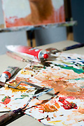 Painter's studio paints and palette scattered on a table