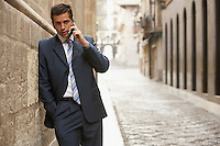Businessman leaning on building in street talking on mobile phone.