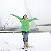 """Nederland Rotterdam 21 december 2007 .."""" Sneeuw maken """" zoals het meisje het zelf noemt. Kinderen spelen in de sneeuw op het Noordereiland  op de achtergrond de Erasmusbrug ..Foto David Rozing"""