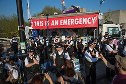 London, UK. 20th April 2019. Large numbers of police officers stand around the stage used by climate change campaigners from Extinction Rebellion on Waterloo bridge as part of an operation to try to clear the bridge of the activists and visitors. The bridge has now been blocked throughout the six days of the International Rebellion called by Extinction Rebellion to demand urgent action to combat climate change by the British government.