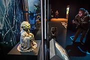 Een vader maakt een foto van zijn zoontje bij een beeldje van Yoda. In Utrecht is de tentoonstelling Star Wars Identies te zien tot en met 11 maart 2018. Op de expositie zijn originele kostuums, rekwisieten en de personages te zien. Daarnaast kunnen bezoekers een eigen Star Wars identiteit maken door hun eigen karakter te combineren met fictieve elementen. Star Wars werd veertig jaar geleden, op 25 mei 1977, voor het eerst getoond op film. De filmserie is nog altijd mateloos populair.<br /> <br /> In Utrecht the exhibition Star Wars Identies is shown. The exhibition shows original costumes, props and the characters. In addition, visitors can create their own Star Wars identity by combining their own character with fictional elements. Star Wars was first shown on film forty years ago, on May 25, 1977. The film series is still very popular.