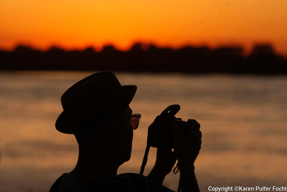 A visitor takes pictures of the Mississippi River at sunset while touring Memphis. Scenes from downtown Memphis, Tennessee.