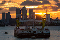 © Licensed to London News Pictures. 29/08/2016. Bank Holiday weekend sunset. Sun setting over the Thames behind Canary Wharf last night (28th August). The Woolwich Ferry is in the foreground. Credit : Rob Powell/LNP