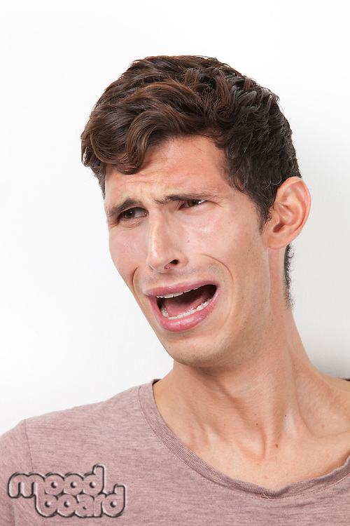 Frightened young man crying against white background