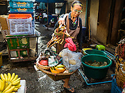 14 DECEMBER 2015 - BANGKOK, THAILAND:  A mango seller walks through Bang Chak Market. The market closes permanently on Dec 31, 2015. The Bang Chak Market serves the community around Sois 91-97 on Sukhumvit Road in the Bangkok suburbs. About half of the market has been torn down. Bangkok city authorities put up notices in late November that the market would be closed by January 1, 2016 and redevelopment would start shortly after that. Market vendors said condominiums are being built on the land.      PHOTO BY JACK KURTZ