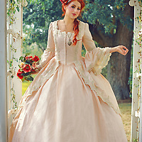 Young woman with long red hair in Regency period dress holding flowers standing under decorative garden arbor