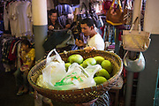"30 JANUARY 2013 - PHNOM PENH, CAMBODIA:  A vendor sells mangoes from a basket atop his head in the Central Market in Phnom Penh. The Central Market (""Psah Thom Thmey"", ""New Grand Market""), is a large market constructed in 1937 in the shape of a dome with four arms branching out into vast hallways with stalls of goods. It opened in 1937, and was the biggest market in Asia at the time; today it still operates as a market. It was renovated from 2009 to 2011.      PHOTO BY JACK KURTZ"