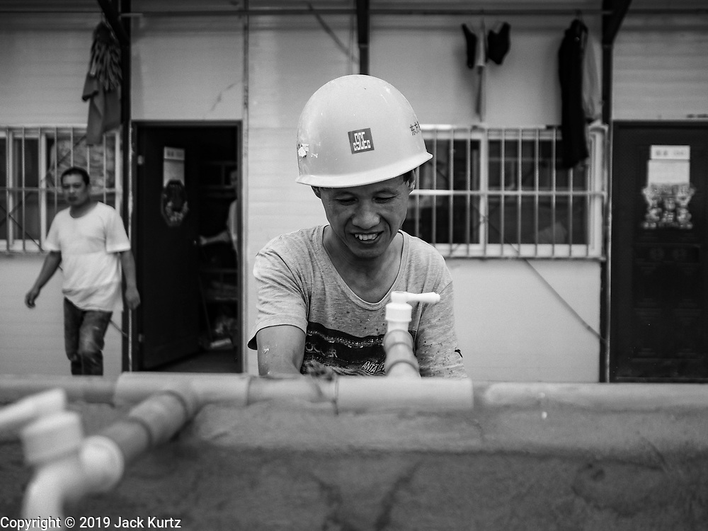 """12 FEBRUARY 2019 - SIHANOUKVILLE, CAMBODIA: A Chinese construction worker washes his dishes in the Chinese workers' labor camp in Sihanoukville. There are about 50 Chinese casinos and resort hotels either open or under construction in Sihanoukville. The casinos are changing the city, once a sleepy port on Southeast Asia's """"backpacker trail"""" into a booming city. The change is coming with a cost though. Many Cambodian residents of Sihanoukville  have lost their homes to make way for the casinos and the jobs are going to Chinese workers, brought in to build casinos and work in the casinos.      PHOTO BY JACK KURTZ"""