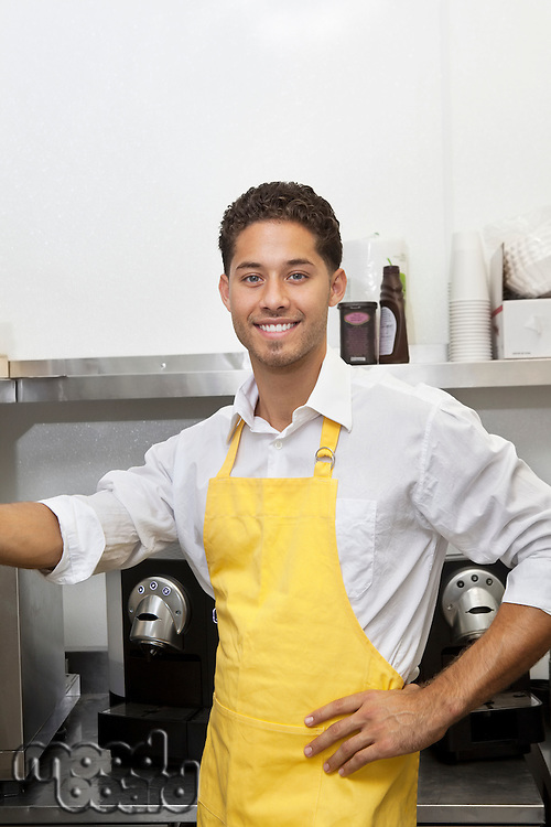 Portrait of young male waiter standing with hand on hip