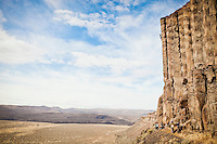 A man climbing a basalt rock cliff in central Washington State, USA.