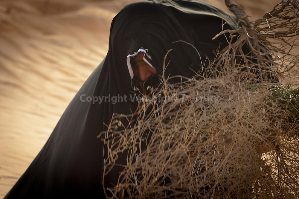 Traditional Abu Dhabi : Bedouin Woman cutting wood in the desert