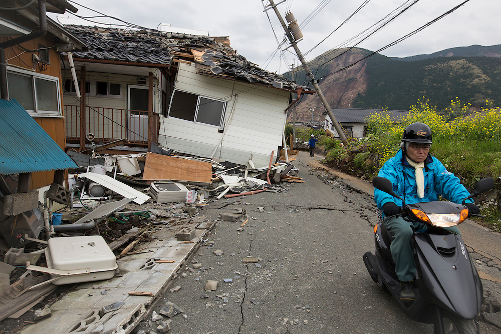 KUMAMOTO, JAPAN - APRIL 18: A local resident passes by collapsed house after an earthquake on April 18, 2016 in Mashiki, Kumamoto, Japan. At least nine people have died in a powerful earthquake, with a preliminary magnitude of 6.4, and followed by magnitude 7.3 quake that struck Kumamoto Prefecture yesterday.<br /> <br /> Photo: Richard Atrero de Guzman