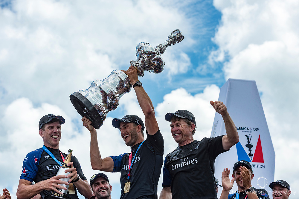The Great Sound, Bermuda, 26th June 2017. Emirates Team New Zealand helmsman Peter Burling and trimmer Blair Tuke and shore crew manager Sean Regan with the America's Cup.