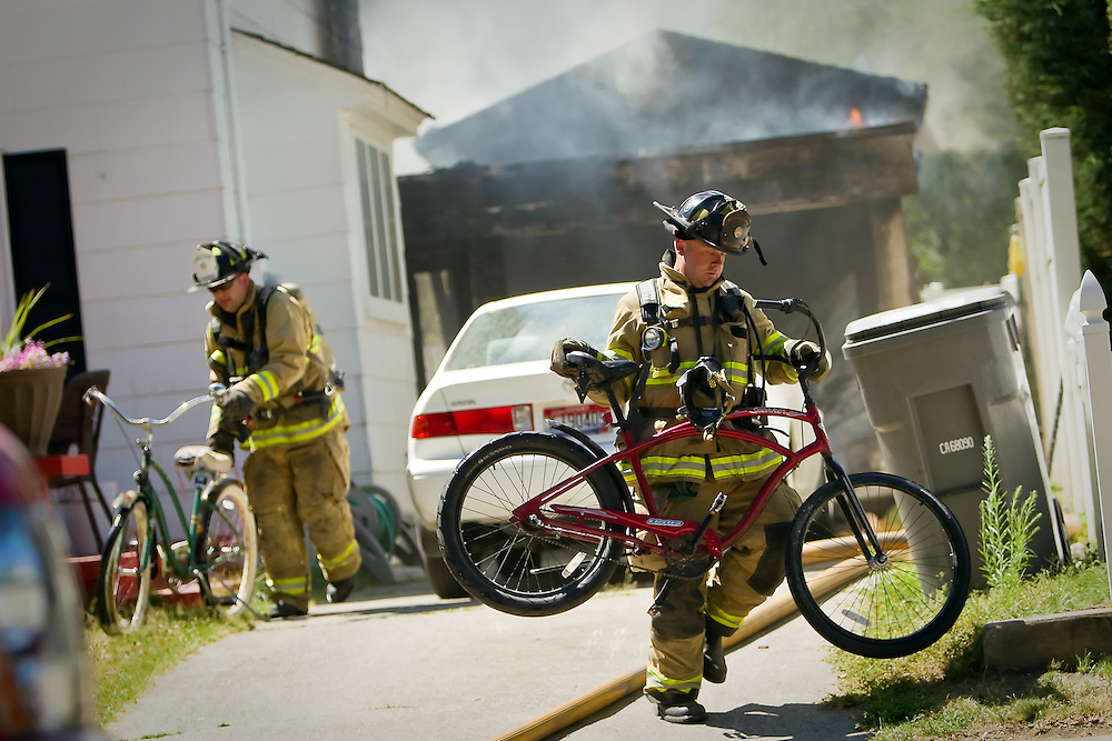 Coeur d'Alene firefighter Nate Hyder carries a bicycle away from the scene of a fire that destroyed a garage.