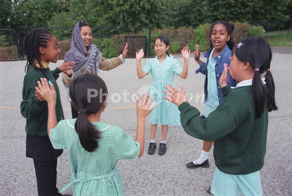 Primary school children standing in circle in school playground playing game,